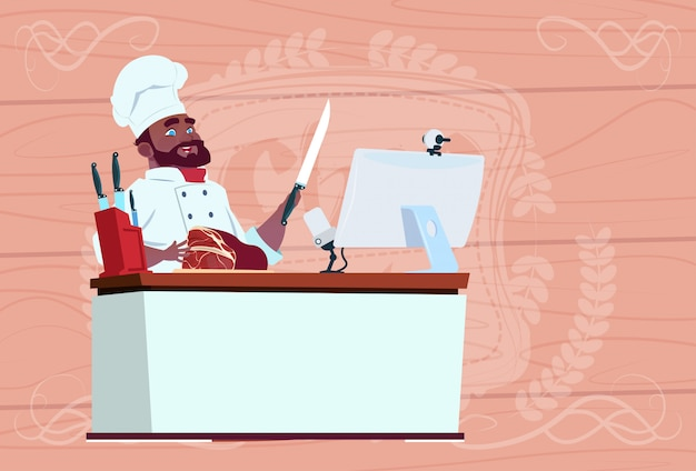 アフリカ系アメリカ人のシェフ料理人のビデオブログを作るコンピュータデスクストリーミング漫画レストランチーフの白い制服のブロガー