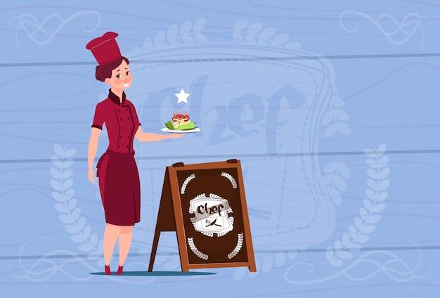 木製の織り目加工の背景の上のレストランの制服を着たサラダ笑みを浮かべて漫画を持った女性シェフクック