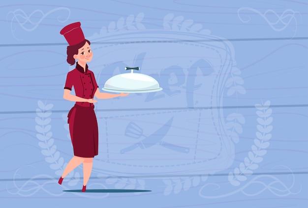 木製の織り目加工の背景の上のレストランの制服を着た漫画の笑みを浮かべて料理と女性シェフクック持株トレイ
