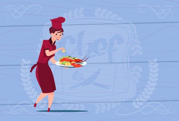 木製の織り目加工の背景の上のレストランのユニフォームのロブスター漫画チーフとトレイを保持している女性シェフクック