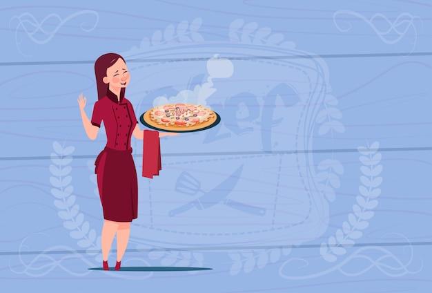 木製の織り目加工の背景の上のレストランのユニフォームでピザ漫画チーフを保持している女性シェフクック