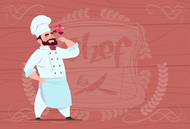 木製の織り目加工の背景の上の白い制服を着たシェフクック幸せな笑みを浮かべて漫画レストランチーフ