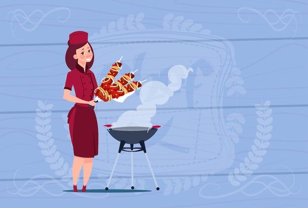 木製の織り目加工の背景の上のレストランのユニフォームでケバブ漫画チーフを保持している女性シェフクック