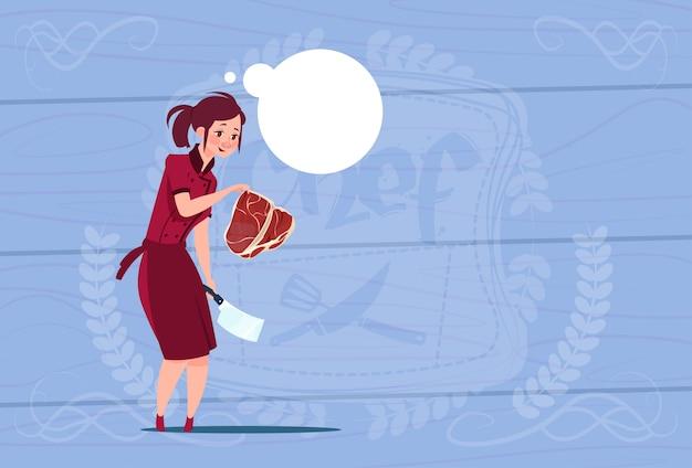 木製の織り目加工の背景の上のレストランのユニフォームで肉漫画チーフを保持している女性シェフクック