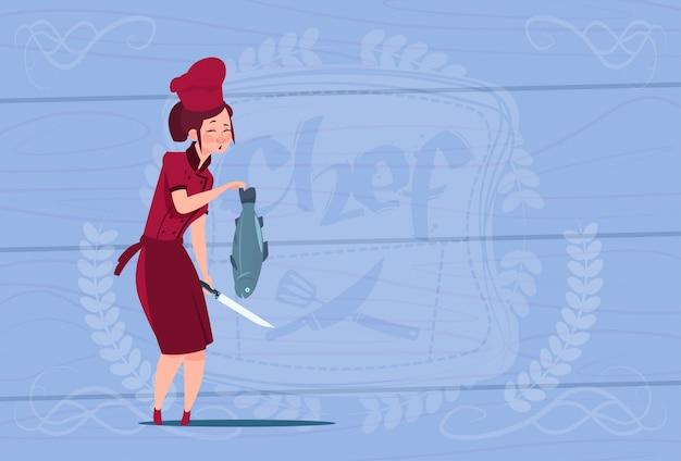 木製の織り目加工の背景の上のレストランの制服を着た魚漫画チーフを保持している女性シェフクック