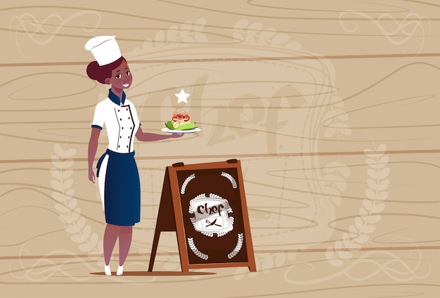 木製の織り目加工の背景の上のレストランの制服を着たサラダ笑みを浮かべて漫画を持って女性のアフリカ系アメリカ人シェフクック