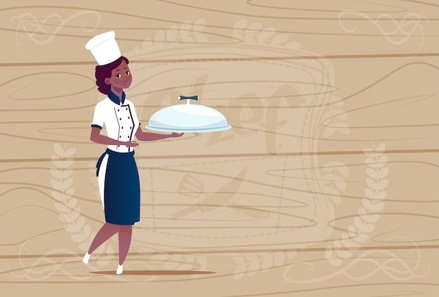 木製の織り目加工の背景の上のレストランの制服で漫画を笑顔で料理を持つ女性のアフリカ系アメリカ人シェフクック