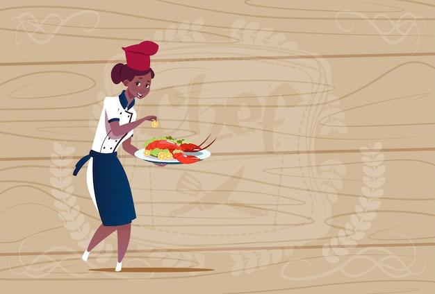 木製の織り目加工の背景の上のレストランのユニフォームでロブスター漫画チーフとトレイを保持している女性のアフリカ系アメリカ人シェフクック