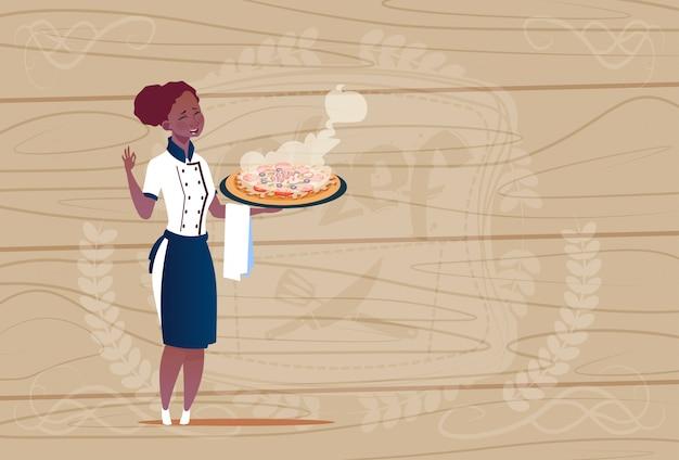 木製の織り目加工の背景の上のレストランの制服を着たピザ漫画チーフを保持している女性のアフリカ系アメリカ人シェフクック