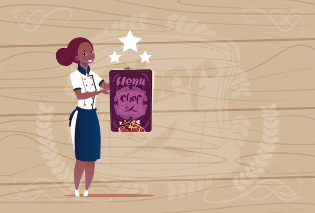 木製の織り目加工の背景の上のレストランの制服を着た最高のシェフ賞ハッピー漫画チーフを保持している女性のアフリカ系アメリカ人料理人