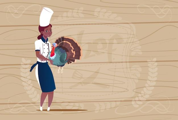 木製の織り目加工の背景の上のレストランの制服でトルコ漫画チーフを保持している女性のアフリカ系アメリカ人シェフクック