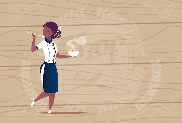 木製の織り目加工の背景の上のレストランの制服を着たスープ漫画のチーフを試飲する女性のアフリカ系アメリカ人シェフの料理人