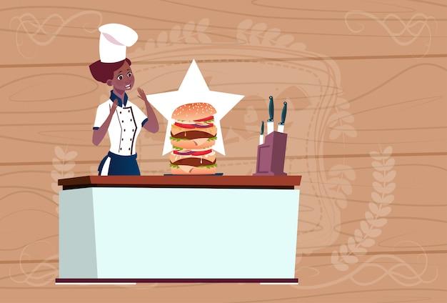女性のアフリカ系アメリカ人シェフの木製の織り目加工の背景上のレストランの制服で大きなハンバーガー漫画チーフを調理