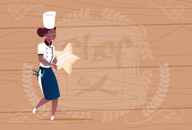 木製の織り目加工の背景の上のレストランの制服を着たスターベストシェフ賞幸せ漫画チーフを保持している女性のアフリカ系アメリカ人クック