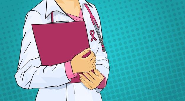 コートの世界にピンクのリボンを身に着けている女性医師癌日コンセプト乳房疾患意識予防