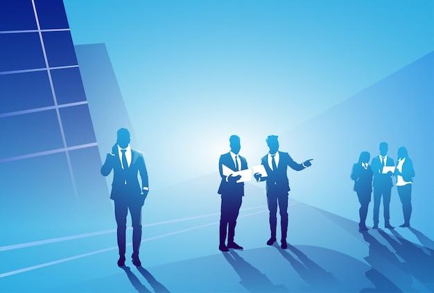 Два бизнесмена силуэта говоря обсуждающ контракт над работающими бизнесменами концепции встречи группы