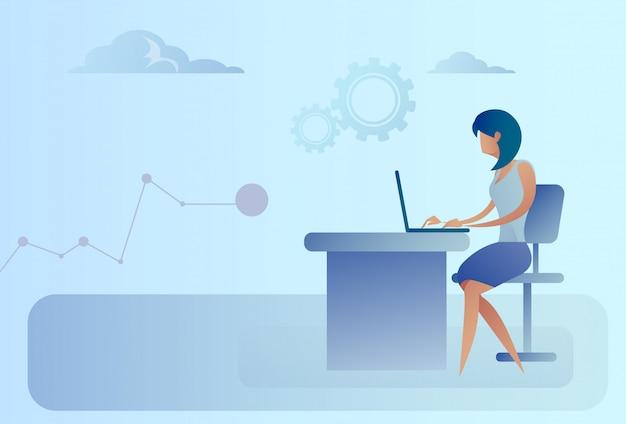 ラップトップコンピューターの作業机に座っている抽象的なビジネス女性