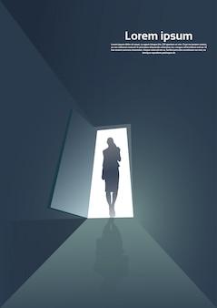 ビジネスの女性のシルエットのドアの入り口に立っている新しい機会の概念