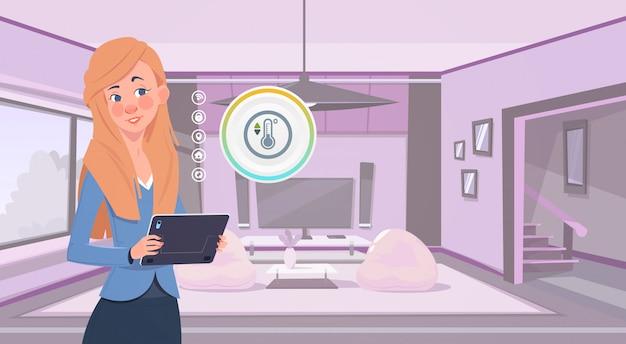 リビングルームの背景上のスマートホームアプリを使用してデジタルタブレットを保持している女性家の監視の概念の現代の技術