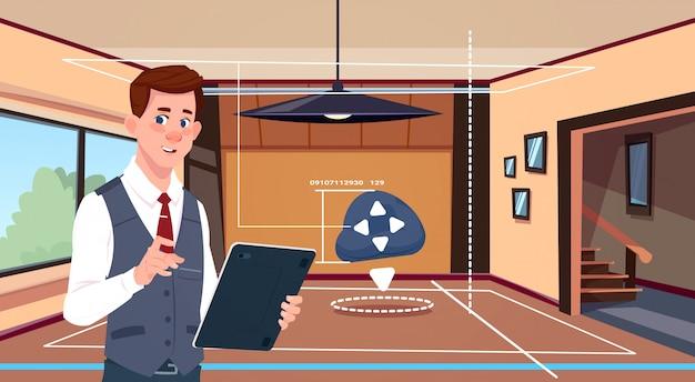 男はリビングルームの背景上のスマートホームオートメーションシステムのデジタルタブレットアプリを使用します。
