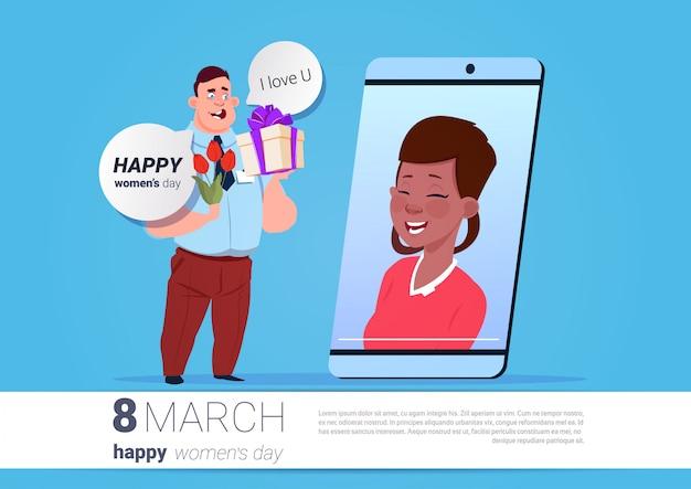 Человек приветствие девушка белый международный женский день онлайн со смартфоном, держа цветы и представить на фоне с копией пространства