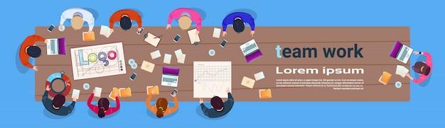 Творческая команда, работающая, сидит за столом в современном офисе. верхний угол обзора. группа деловых людей. мозговой штурм. горизонтальный баннер.