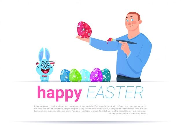 Человек крася яйца на фоне счастливой пасхи шаблон с забавным кроликом