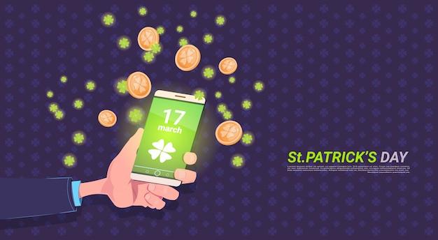 ハッピーセントパトリックデーの背景の上にクローバーの葉と黄金のコインを持つスマートフォンを持っている手