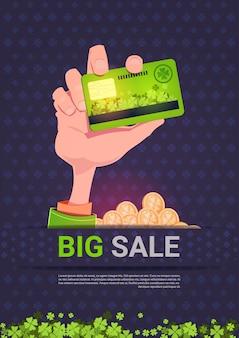 大セール聖パトリックの日の休日テンプレートの背景の上にクレジットカードを持っている手