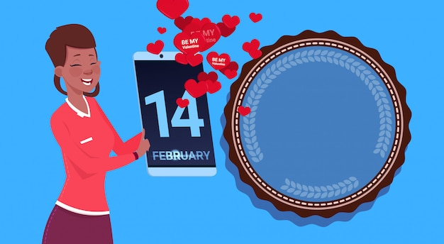 アフリカ系アメリカ人の女の子が青い背景上幸せなバレンタインデーおめでとうを送信するデジタルタブレットを保持します。