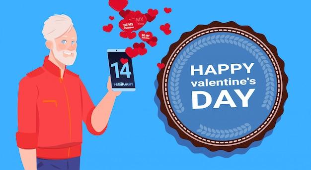 年配の男性が青い背景上幸せなバレンタインデーおめでとうを送信するスマートフォンを使用します。