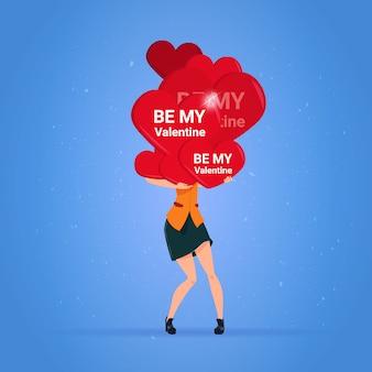 Счастливая поздравительная открытка дня святого валентина женщина, держащая стек любовной праздничной концепции сердец