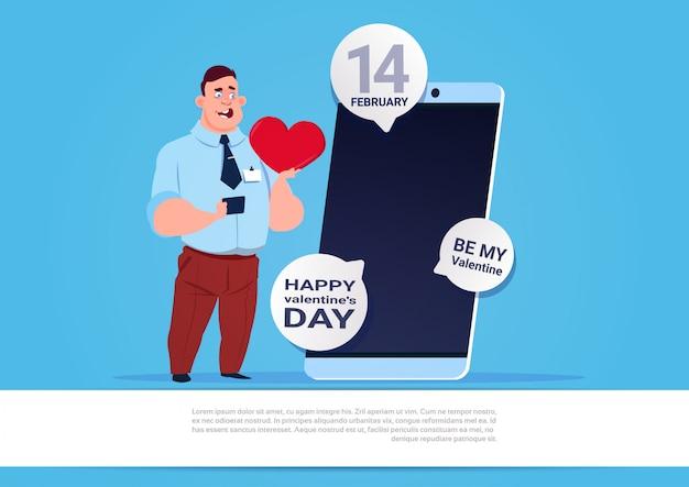 男は青い背景上幸せなバレンタインデーおめでとうを送信するスマートフォンを使用します。
