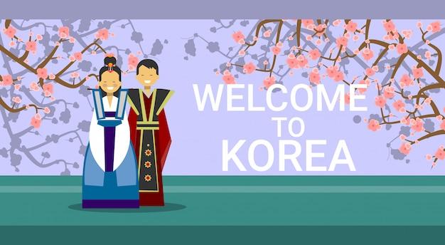 Путешествие в южную корею, счастливое корейское купе в традиционных костюмах над цветами сакуры