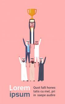 ゴールデンカップ、イスラム教徒のビジネスの男性の成功の概念を保持している成功したアラブのビジネスマンのグループ