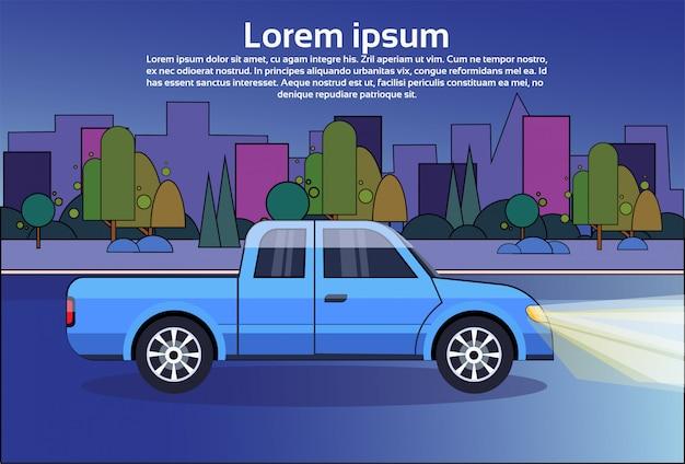 都市の建物の上の夜の道路上のピックアップトラック青い車