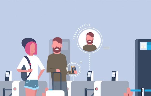 登録を待って空港でチェックインのためのスキャナーを通って来る手荷物を持つ観光客のカップル
