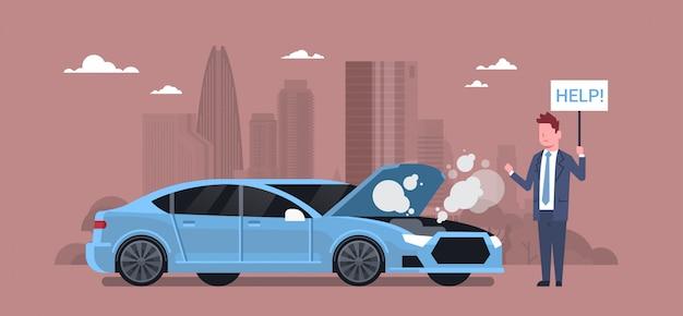 Человек с разбитым автомобилем держит знак помощи на дороге над городом силуэт