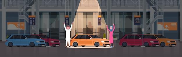 新しい車のセット上のディーラーセンターショールームで新しい車を提示するアラブの売り手のカップル水平図