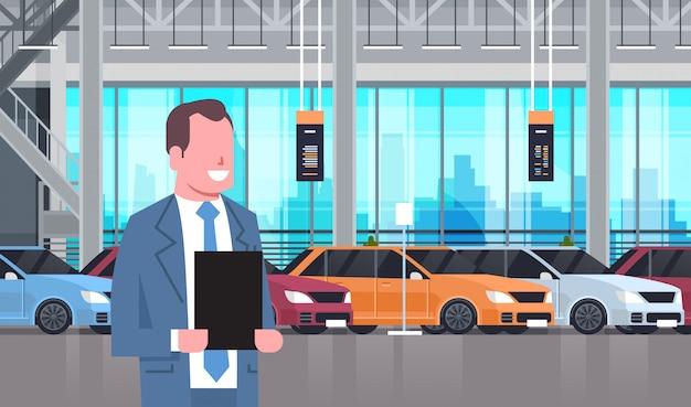 新しい近代的な車のセットの上の車ディーラーセンターショールームインテリアの売り手男