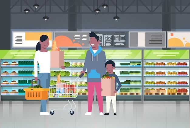 Семья афроамериканцев делает покупки в супермаркете и покупает продукты