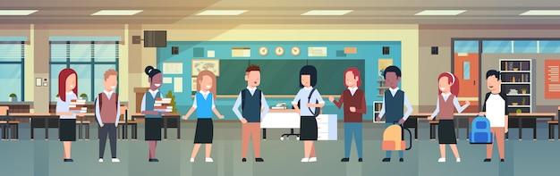ミックスレースの学生のグループ、学校の近代的なクラスの部屋で多様な生徒との教室のインテリア
