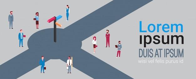 方向標識の周りのビジネス人々のグループ