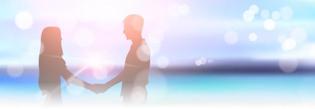 ぼやけている美しい海辺のビーチのボケ味に手を繋いでいるシルエットカップル
