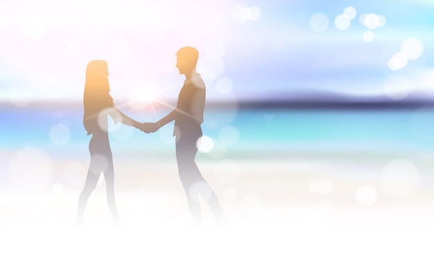 美しい海のビーチのボケ味の背景に手を繋いでいるシルエットカップル