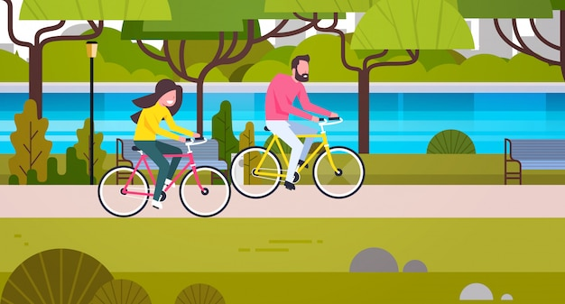 カップルの公園で自転車に乗る男と女の屋外サイクリング
