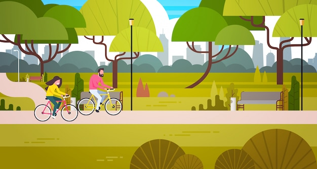 都市建物のスカイラインの上の公共の公園でカップルの自転車に乗る男と女の屋外サイクリング