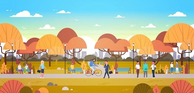 街のスカイラインの上を歩く秋の都市公園で屋外でリラックスしている人々乗馬自転車と通信