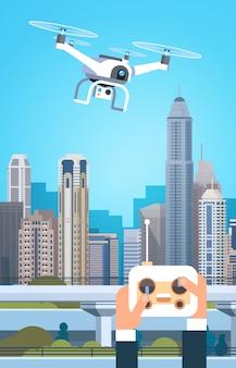 近代的なドローンのために両手リモートコントローラーが都市の建物の上を飛ぶ