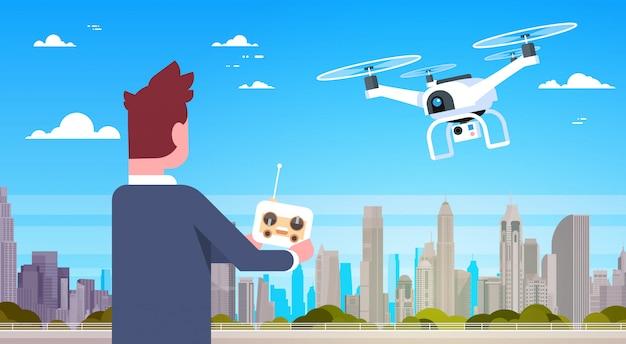 近代的なドローンのリモートコントローラーを保持しているビジネスマンが都市の建物を飛ぶ